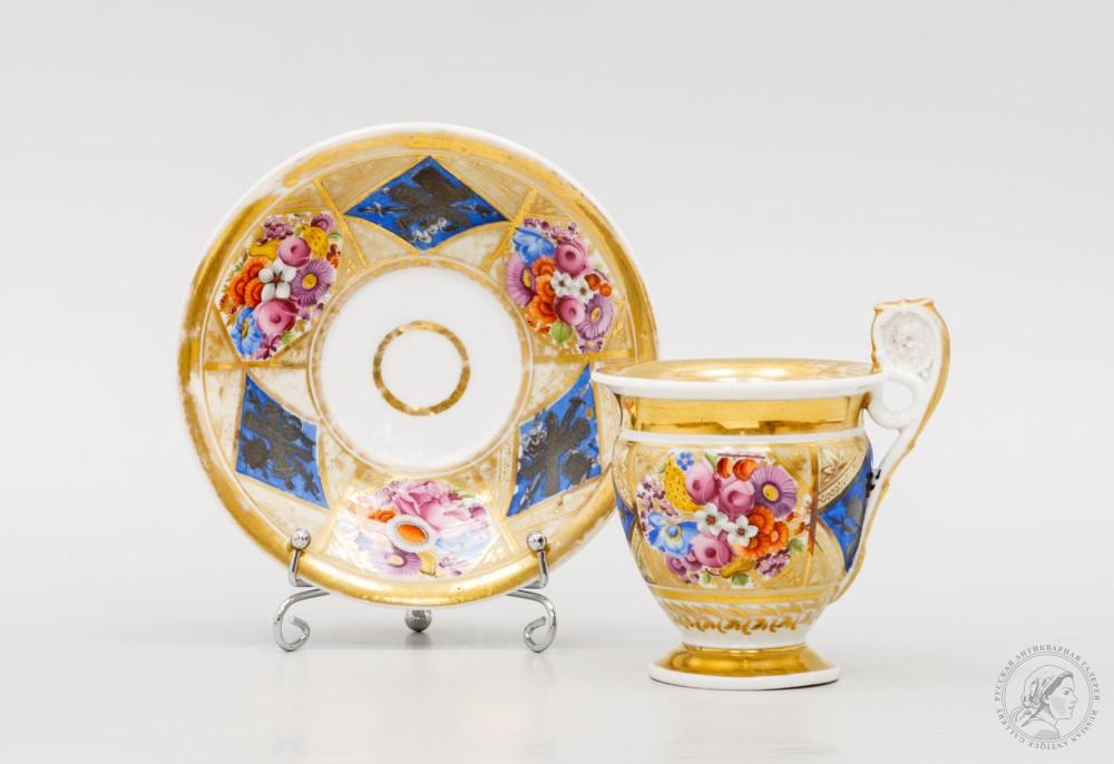 Фарфоровая чайная пара, украшенная чередующимися изображениями цветов и военной арматуры